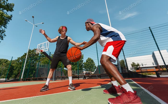 Two young basketball players in action at outdoor sports court