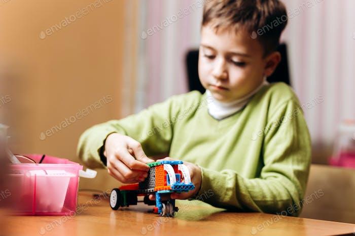 Junge in grünen Pullover gekleidet sitzt am Tisch in der Robotikschule und macht einen Roboter aus dem