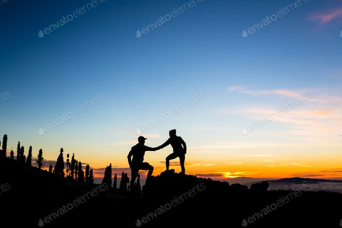 Teamwork couple climbing with helping hand