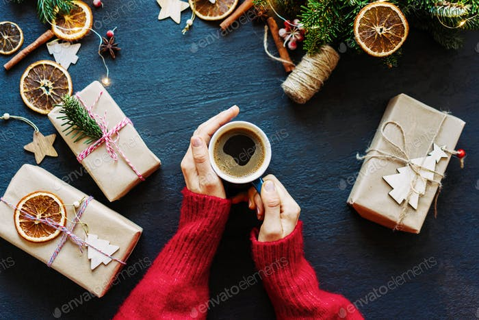 Female hands holding a mug of coffee, Christmas decor and wrapped gifts on the table, celebration