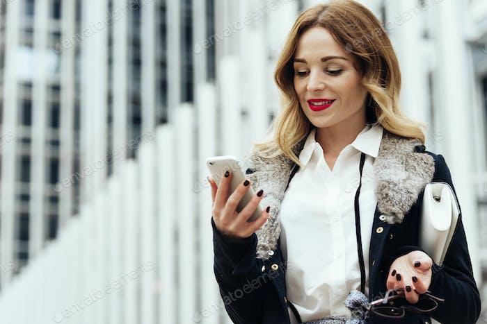 Молодая умная профессиональная женщина читает по телефону.