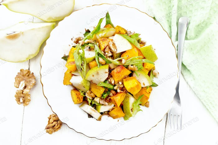 Salad of pumpkin and pear in plate on board top