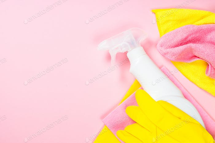 Cleaning spray, cloth and gloves on pink background