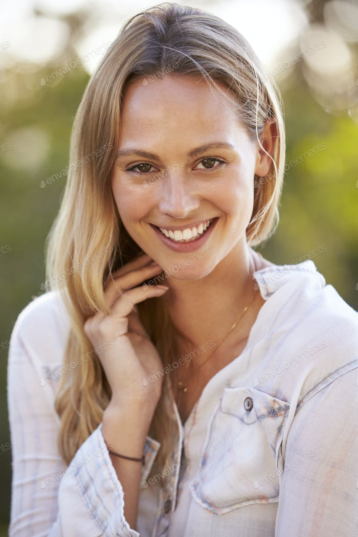 Portrait of young white woman smiling outdoors
