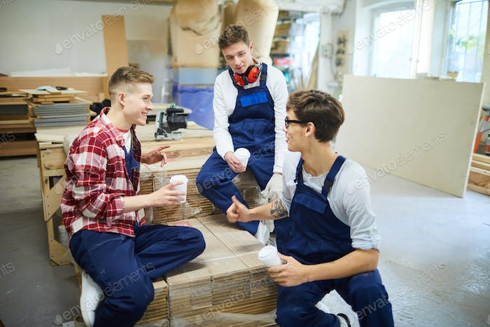 Content friends sharing news at break in carpentry shop