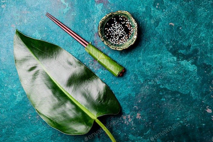 Stäbchen und Soysauce Sojasauce mit weißem Sesam auf türkisfarbenem Hintergrund mit tropischen Blättern