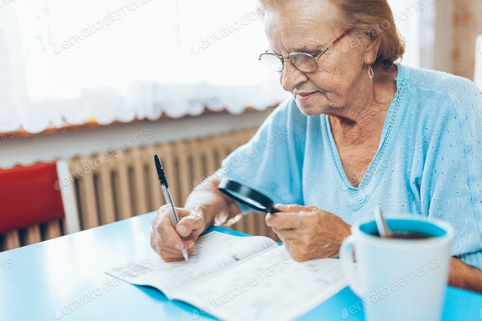 Senior woman enjoys solving a crossword puzzle