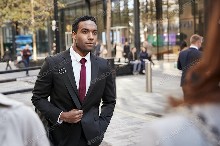 Young black businessman walking in a street in the city, selective focus