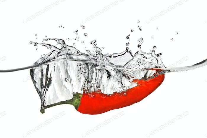 roter Pfeffer in Wasser mit Spritzer auf weiß isoliert