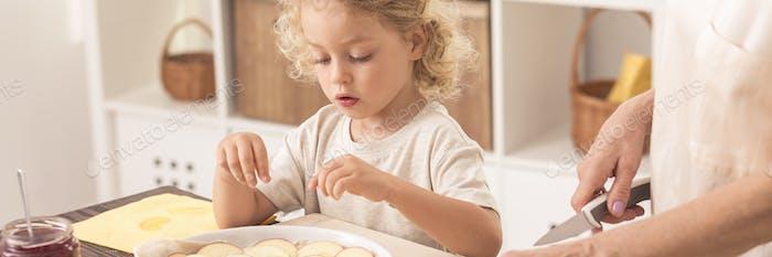 Child baking cake with grandma
