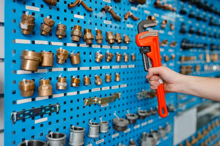 Plumber holds pipe wrench in plumbering store