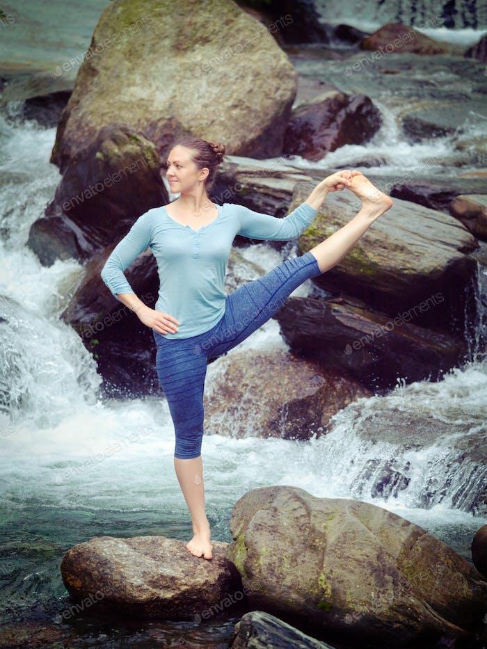 Frau tun Ashtanga Vinyasa Yoga Asana im freien an Wasserfall