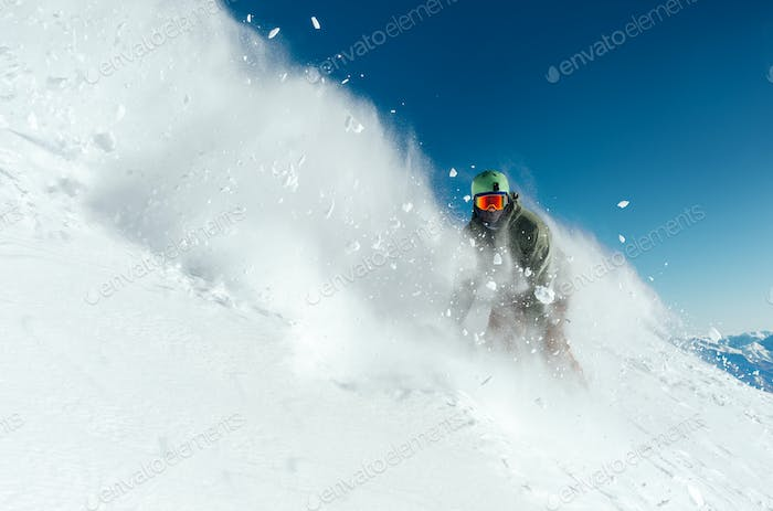 man snowboarder is going very fast in   stream of snow avalanche
