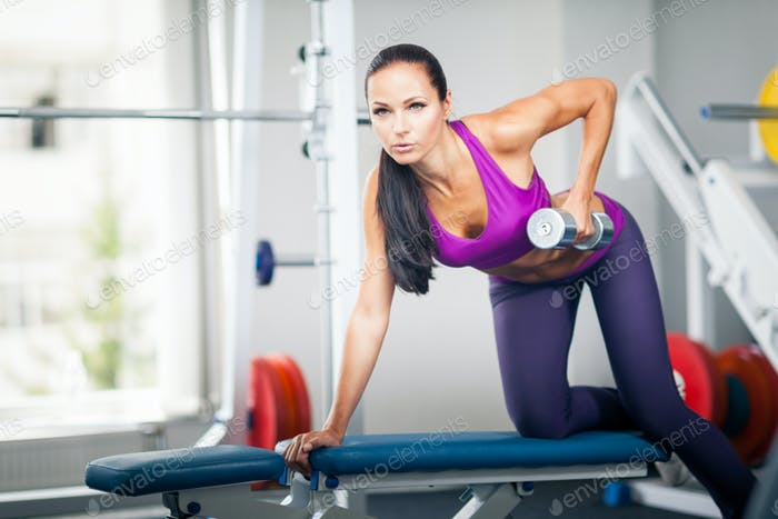 Beautiful lady working out with dumbbell