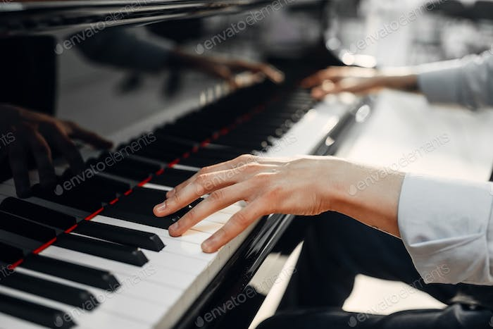 Male pianist hands on grand piano keyboard