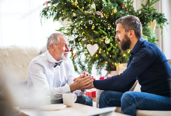 A senior father and adult son sitting on a sofa at Christmas time, looking at each other.