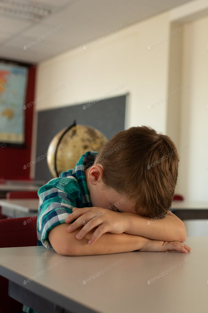 Boy sleeping with his head on his crossed arms in a classroom at elementary school