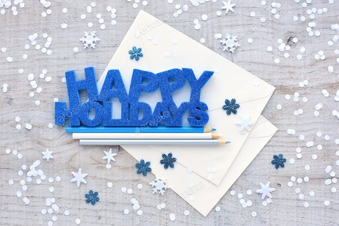 """Greeting """"Happy Holidays"""", pencils, envelopes and snowflakes on"""