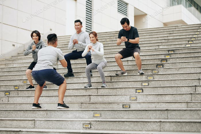 Leute machen Kniebeugen mit Trainer im Freien