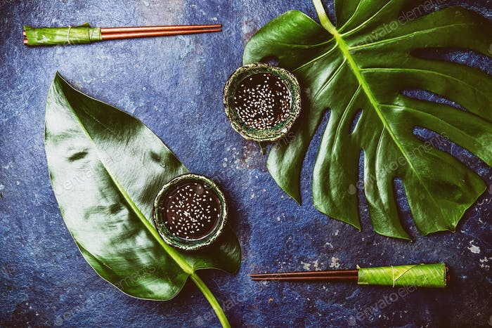 Chopstick and soysauce soy sauce with white sesame on turquoise background with tropical leaves