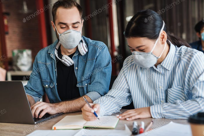 Photo of multinational students in medical masks studying with laptop