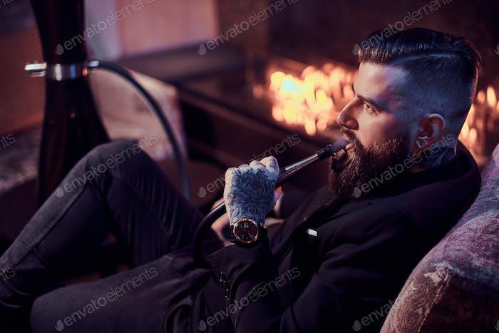Attraktive präparierte Mann entspannt sich in der Lounge in der Nähe von Kamin beim Rauchen Shisha