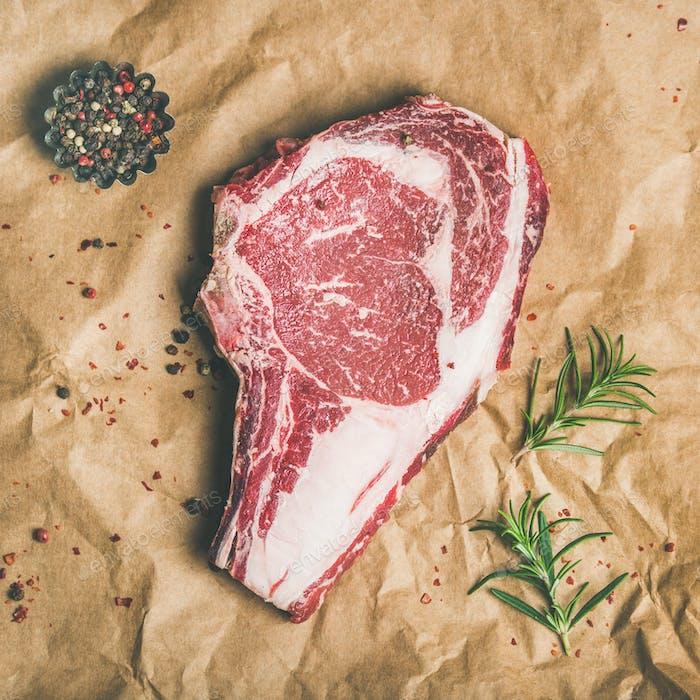 Raw steak rib-eye with seasoning on craft paper, square crop