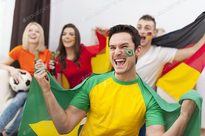 Aufgeregt Brasilianer Mann mit ihren Freunden jubeln Fußballspiel
