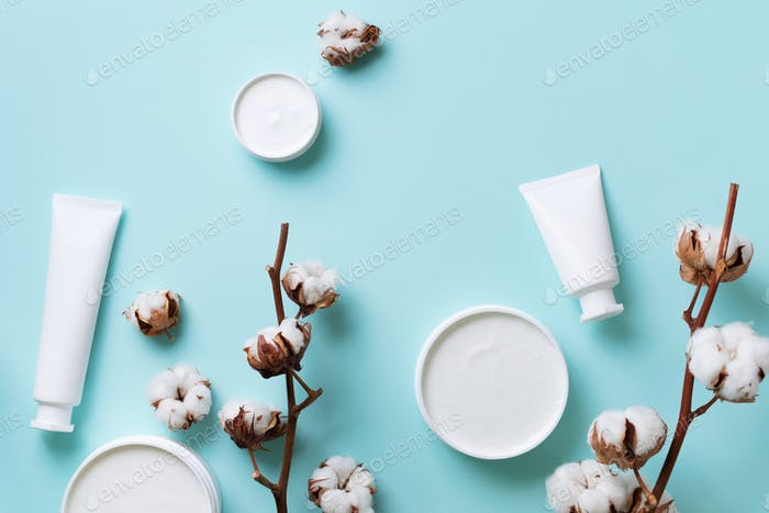 Fluffy cotton flowers, face cream, body butter on blue background with copy space. Cosmetics, beauty