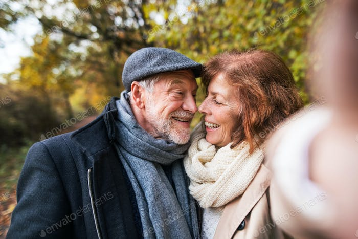 Senior couple in love in an autumn nature, taking selfie.