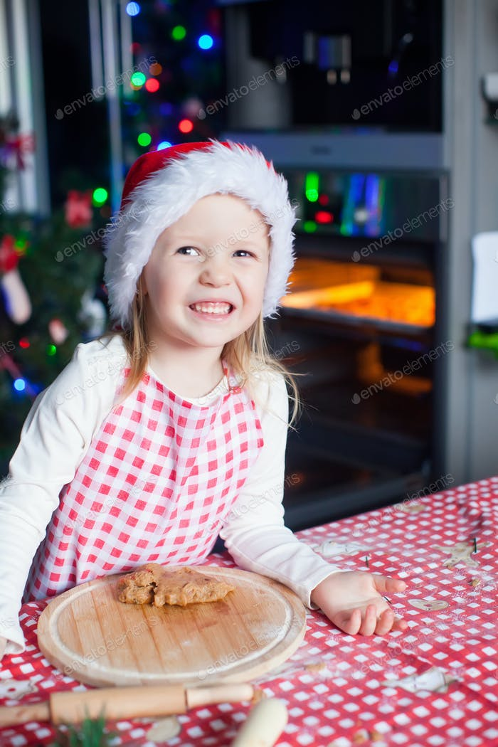 Portrait of happy cute little girl in the kitchen baking gingerbread