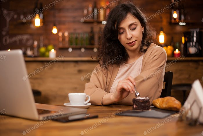 Beautiful woman eating delicious chocolate cake in a coffee shop