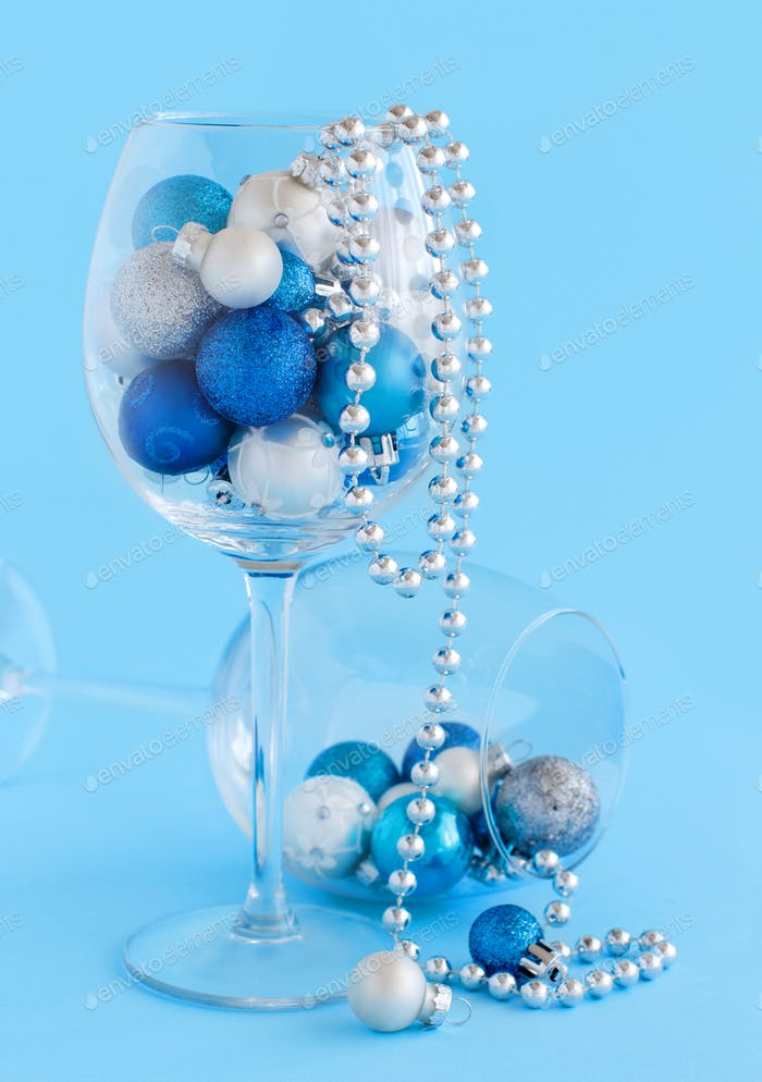 Christmas baubles in a wine glass on a light blue background