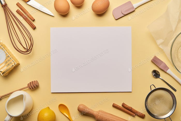 top view of bakery ingredients and cooking utensils around blank card