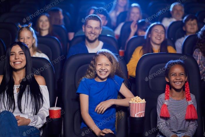 Multiracial audience enjoying cartoon in cinema hall