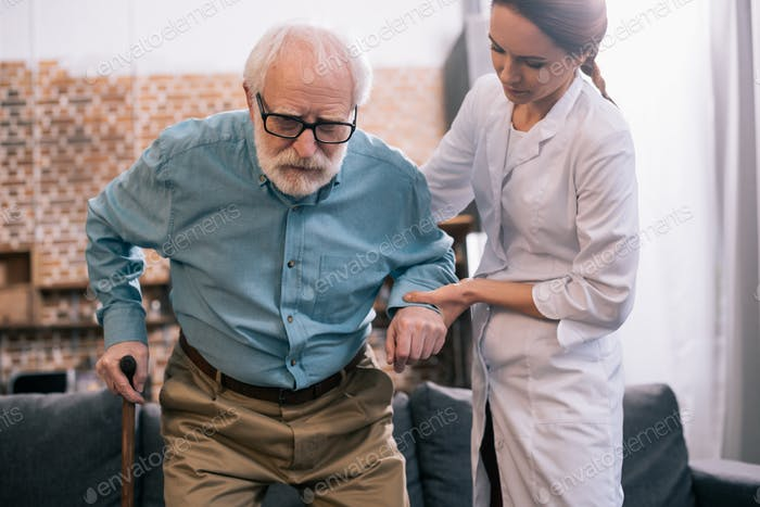 Old man leaning on cane and female doctor hand