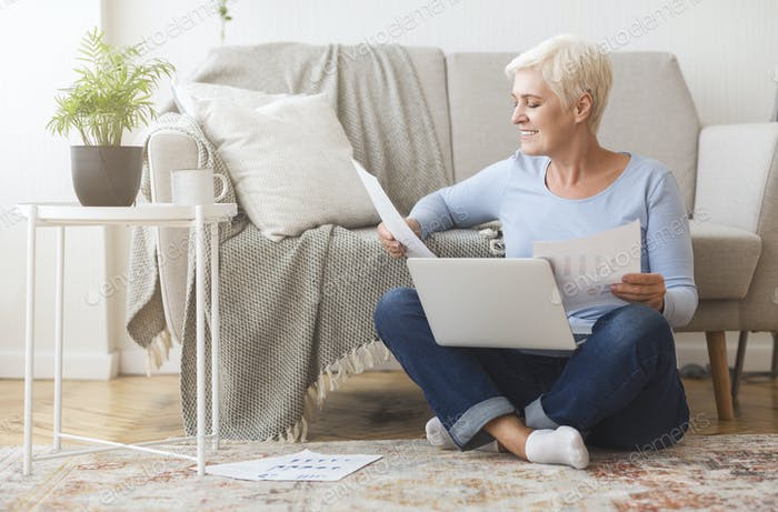 Aged financial consultant sitting on floor with laptop at home
