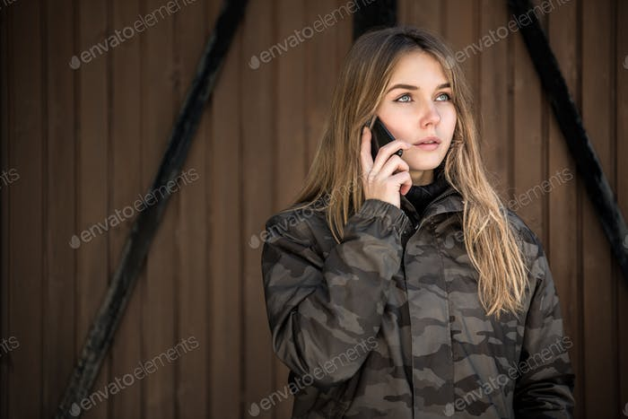 портрет Молодая красивая женщина зимой в снегу с помощью мобильного телефона