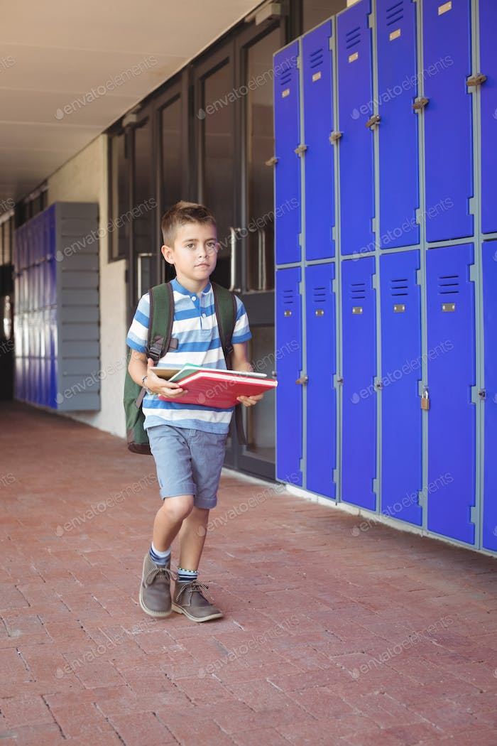 Full length of boy carrying books in corridor