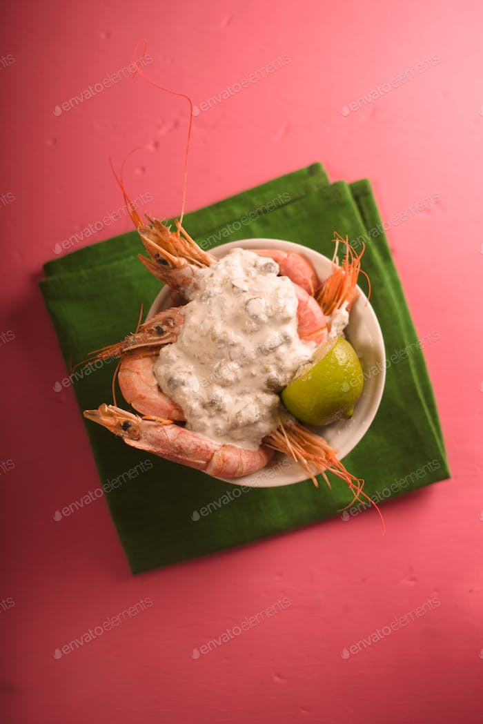 Serving shrimps with sauce and lime in a ceramic bowl