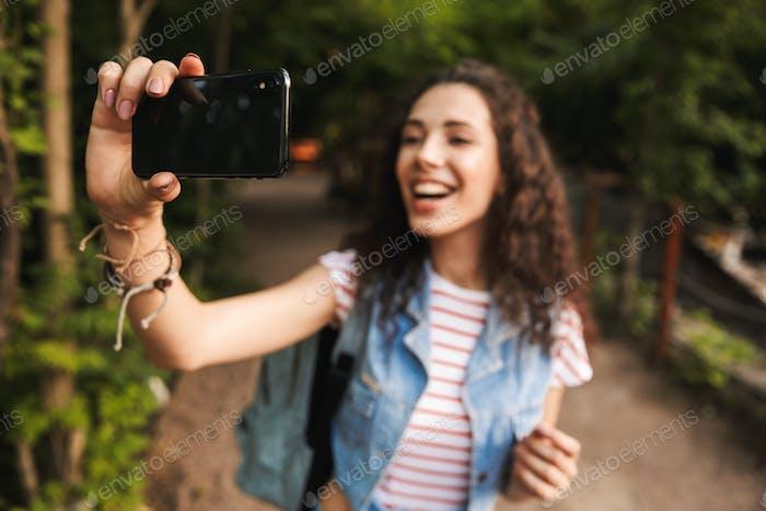 Verschwommenes Foto von Brünette hübsche Frau 18-20 mit Rucksack, Smili