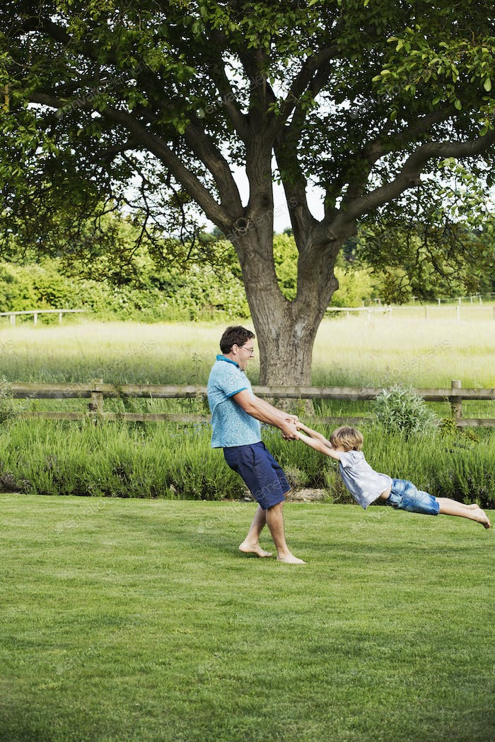 Man standing on a lawn in a garden, holding a boy by his hands, spinning and whirling him around.