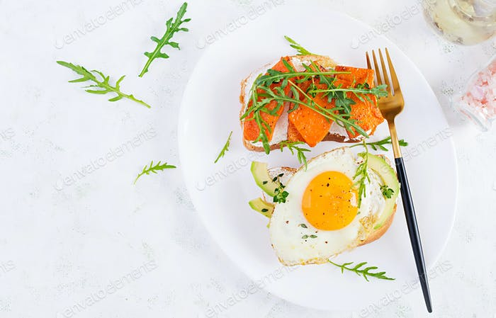 Sandwich with avocado and fried egg, sandwich with fried sliced pumpkin