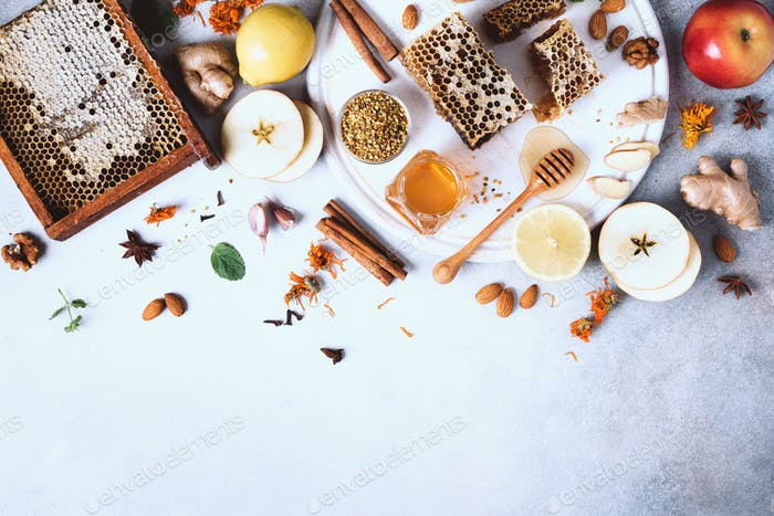 Autumn picnic. Herbal tea, honey and bee products, apple, lemon, calendula, spices on grey concrete