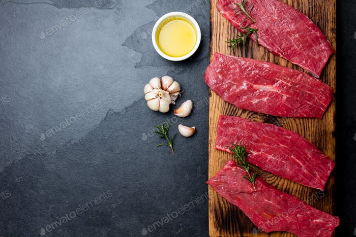 Beef tenderloin on wooden board, spices, herbs, oil on slate gray background.