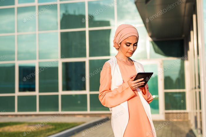 beautiful arabian girl with tablet computer. Muslim woman.