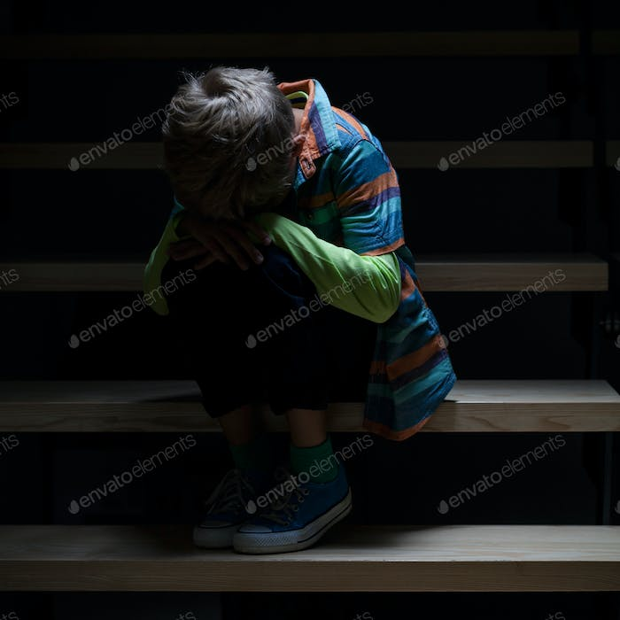 Crying boy sitting on staircase
