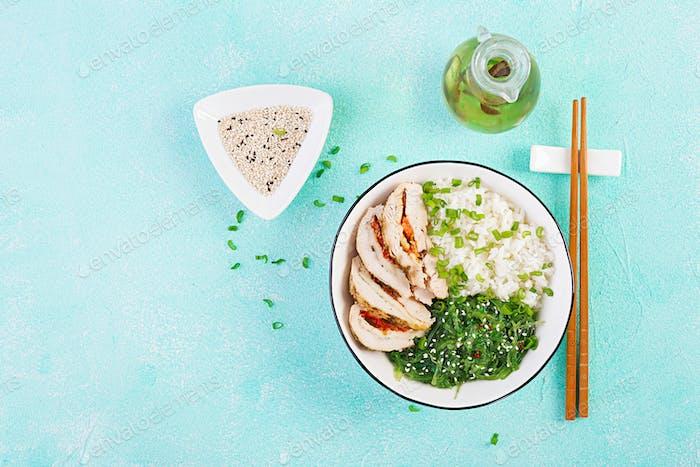 Gesunder Salat in einer weißen Schüssel, Stäbchen. Hähnchenbrötchen, Reis, Chuka und grüne Zwiebel.