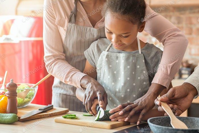 Begeisterte Mädchen schneiden Gurke unter Mama Aufsicht