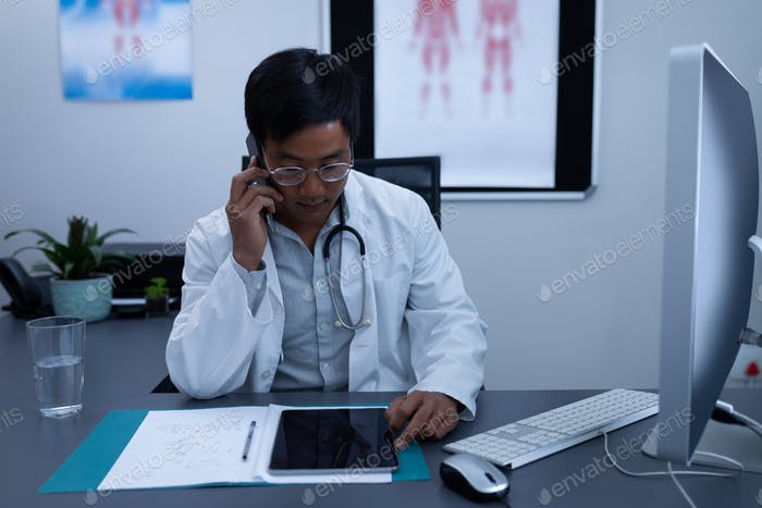 Male doctor talking on mobile phone while using digital tablet in clinic at hospital